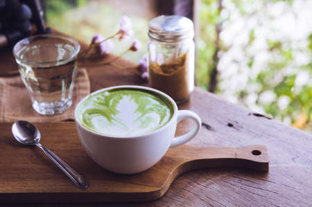 green tea hot drink latte white cup on wood table Stok Fotoğraf
