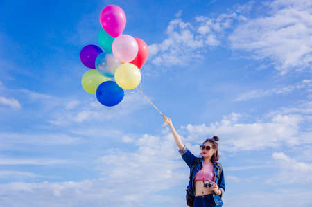 Girl holds the balloons with the sky background
