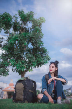 A traveler young girl sitting under a tree relax time  and looing view place with a big bag