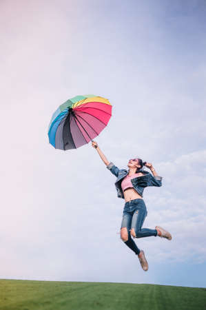 jumping girls and hold up umbrella color the sky background nature park season rainy day Stock Photo