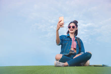 Woman sitting on green grass smiling on the day and photograph selfie  smartphone