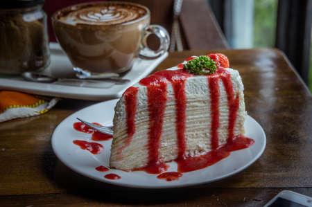 strawberry crape cake on wood table in coffee shop , dessert tasy cake