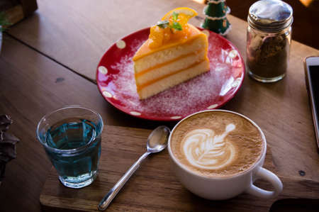 coffee aroma latte art cup and tasty christmas cake on wood table relaxtime in cafe coffee shop Stock Photo