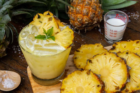 Pineapple juice and pineapple slices cut into pieces on a wooden table. Healthy wood fiber helps to reduce food. Pineapple juice Contains fresh milk, nectar and salt.