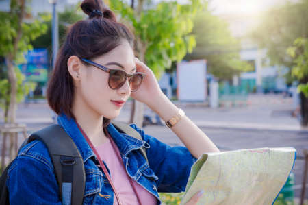 girls looking at destination and hold a map on street Stock Photo
