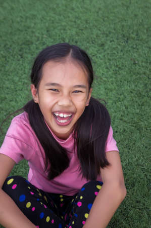 asian girls siting and smile looking at on the artificial grass Field background