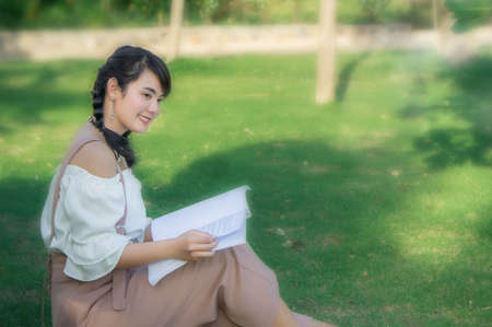 the asian girls sitting in the park and reading a book on the  day Stock Photo