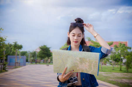 Female tourists Looking for destinations on the map in the town