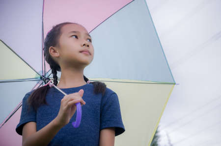 little girls hold umbrella smile and looking at on the  rainy season Stock Photo