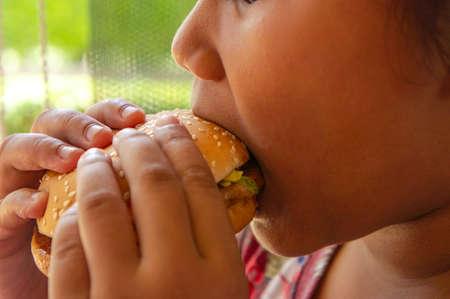 Kids enjoy eating a hamburger junk food   No health benefits for kid Stok Fotoğraf