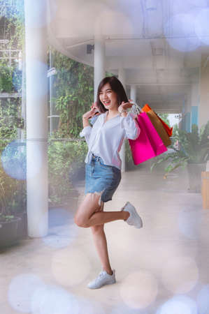 woman holding shopping bags and walking smile happy on the day