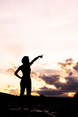woman Stand and looking at and pointing to the horizon silhouette