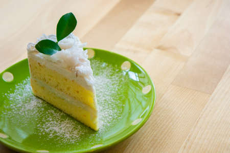 coconut cake on dish green on wood table