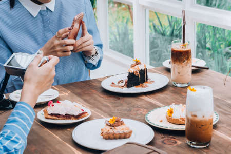 women talking and take a photo dessert and food in cafe restaurant, enjoy eating Stock Photo