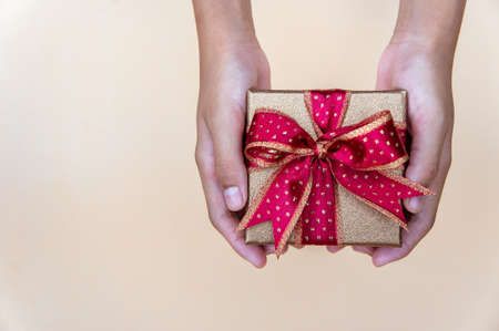 Golden gift box with red ribbon , giving gift box for special person on special day