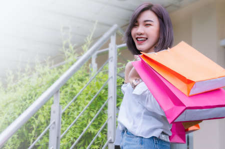 Happy woman smile and holding shopping bags shopping on the day Stock Photo