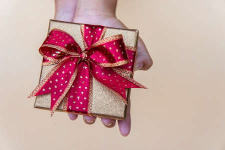 Golden gift box with red ribbon