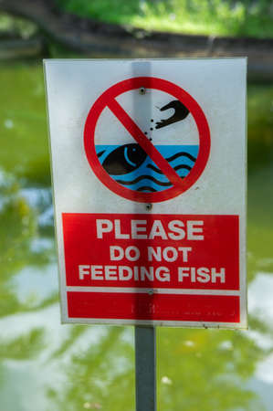 Label please do not feeding fish in the park Stock Photo