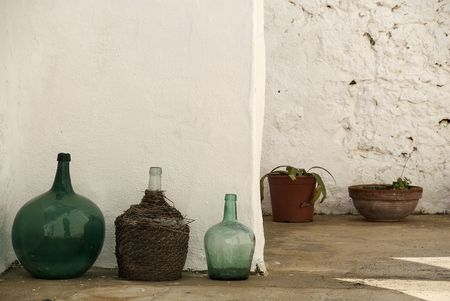demijohn: wine carboys (or demijohn) in front of a white sunny wall