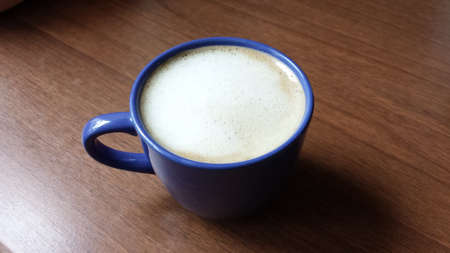 agitation: Blue cup of coffee and frothed milk on a brown counter Stock Photo