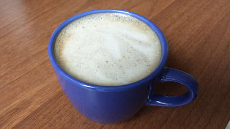 Blue cup of coffee and frothed milk on a brown counter Stock Photo