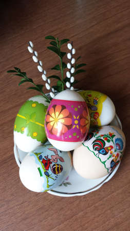 catkins: The five colorful Easter eggs on a plate with boxwood and catkins Stock Photo