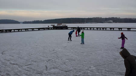 skaters: Olsztyn, Poland - January 7, 2017: Skaters on a frozen lake on a cloudy day