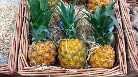 Three small pineapples in a wicker basket Reklamní fotografie - 85040480