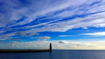 Vuurtoren en golfbreker tussen de zee en de lucht Vuurtoren en golfbreker tussen de zee en de lucht