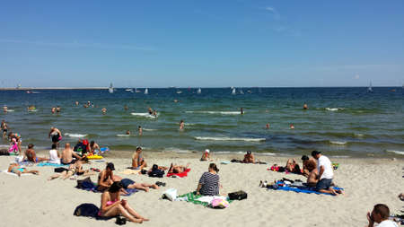 Gdynia, Poland - June 10, 2018: People sunbathe on the beach and bathe in the sea.
