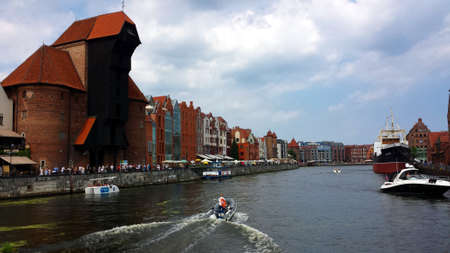 Gdansk, Poland - August 4, 2018: A classic view of the old city of Gdansk on the Motlawa River. Tourists walk along the waterfront.