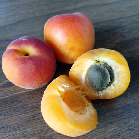 Three apricots, including one split with pit.