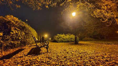 Park in the evening without people, a lit lantern. Foto de archivo