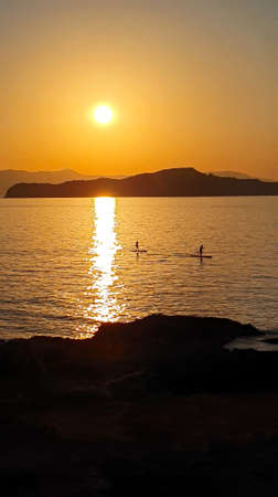 A man is sailing on a board with an oar during a beautiful golden sunset over the water on Crete, Greece.
