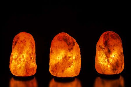 Three salt lamps on black background
