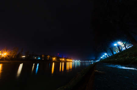 Night city photographed at long exposure. Water, glare and night lights. Architecture and buildings of the city of Uzhgorod. Beautiful night photos without people. No one is on the street Stock Photo
