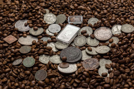 Soviet Union coins fall on coffee beans. Two dollars in silver. Charms and bark of the Mamvri oak. Washingtonia Leaflet. Flatley. Souvenirs on a dark background. Brown background