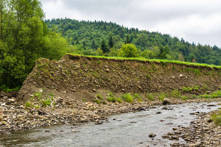 Landslide in the village. Rocks and ground are destroyed. Sunny weather. Plants die. Cataclysms. The texture of the stones. Rockfalls. Mud. Destroyed rural road landslide damaged in powerful flood