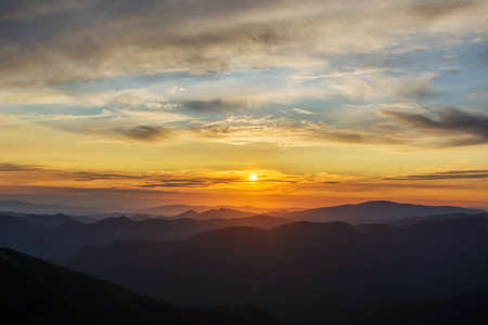 The first or last rays of the sun on a mountain pass. Morning and evening in nature. Colorful sunset and sunrise over the mountain hills. Carpathians in summer and autumn