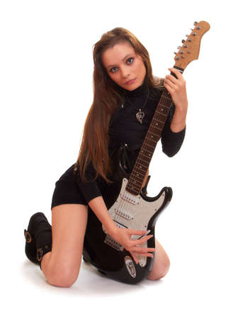 Beautiful young woman is sitting on a white background embracing rock guitar Stock Photo - 8225402