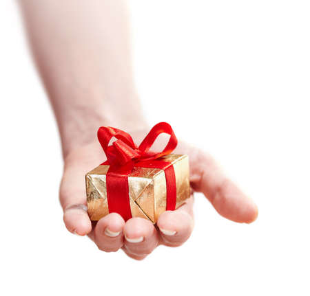 fmale: Fmale hand giving gold present box with red ribbon