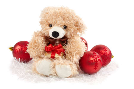 Teddy bear sitting and holding golden gift box surrounded by christmass ball decorations photo