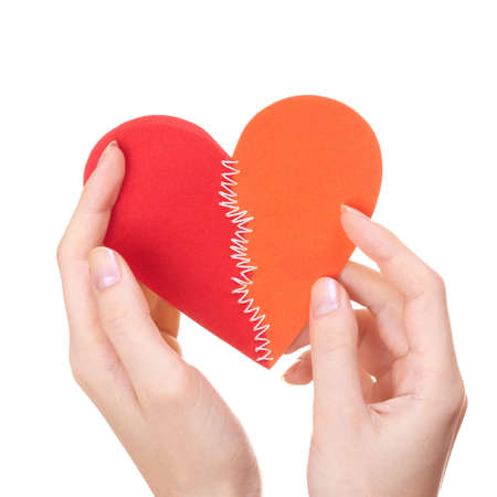held: Woman holding broken heart stitched from two pieces in Saint Valentine day