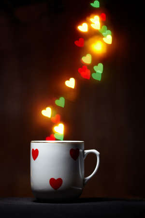 valentine day cup of coffee: Mug emits steam of glowing hearts on dark background with copy space