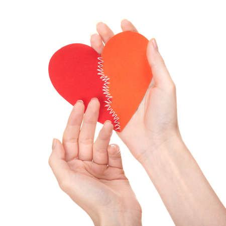 Concept of care. Woman strokes broken heart stitched of two halves. photo