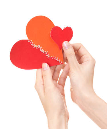 Woman holds big stitched heart and injured little heart in her hands Stock Photo - 9139625