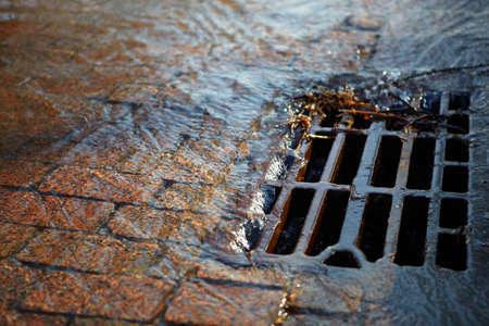 riool: Gesmolten water stroomt het Putdeksel op een zonnige lentedag Stockfoto