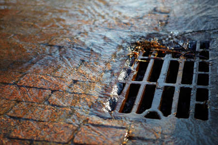 sink drain: Melted water flows down through the manhole cover on a sunny spring day