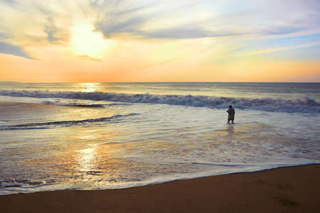 drowns: Young man walking on shore of the ocean with a camera in his hands against the rising sun. He nearly drowns in huge waves at high tide.