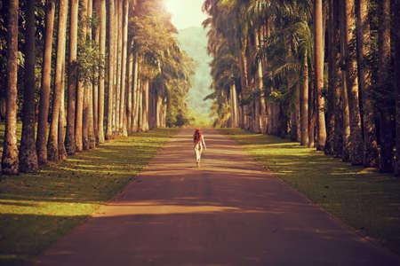 길을 걷고 소녀는 멀리 산에 야자수에 둘러싸여